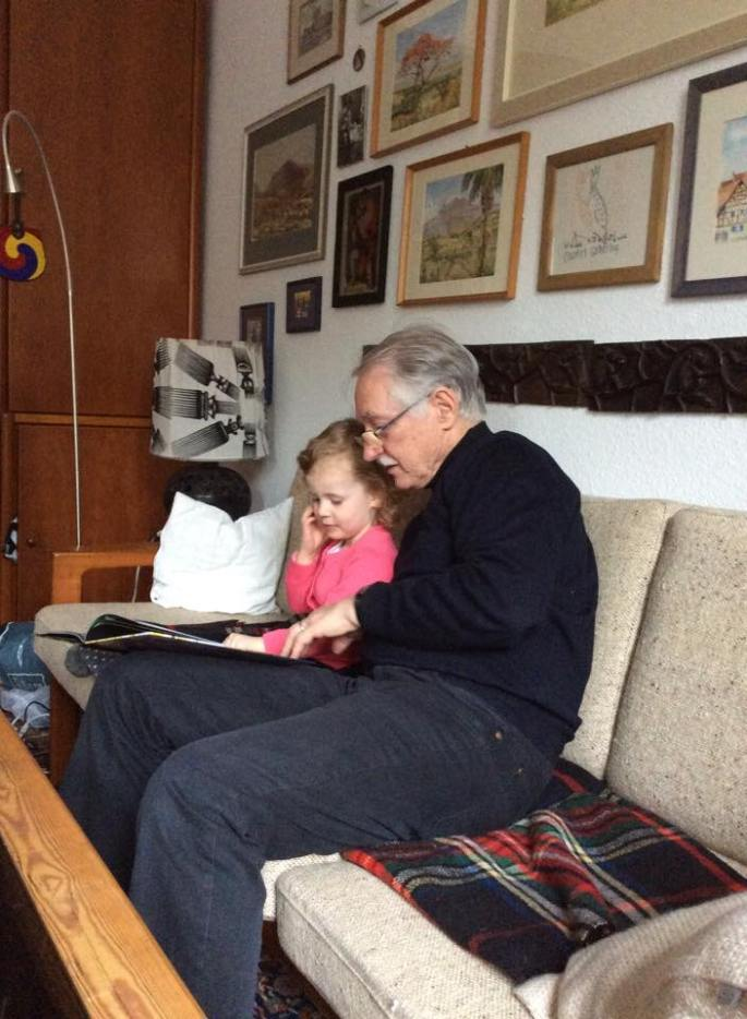 Grandpa reading to his grand daughter