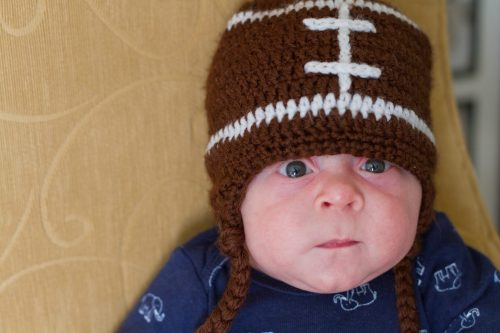 Baby with football hat on