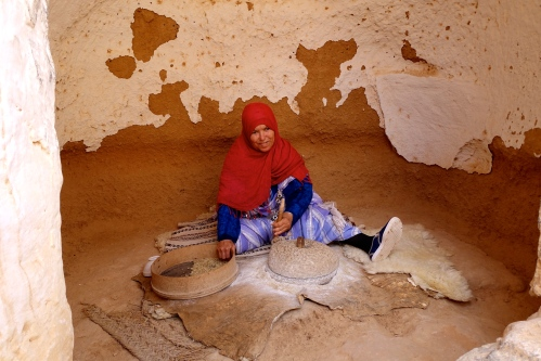 Woman grinding grain with mill stones