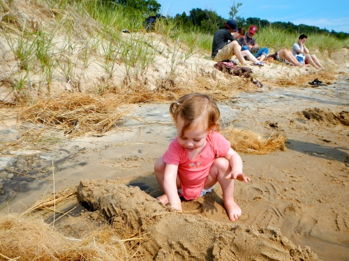 Baby playing in sand at Hoffmaster State Park