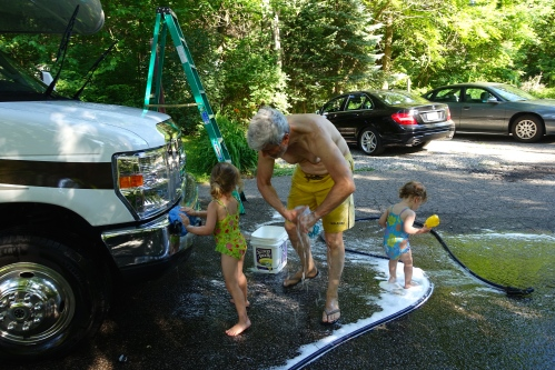 Washing the car with little girls helping