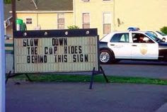 Slow Down. The cop is hiding behind this sign