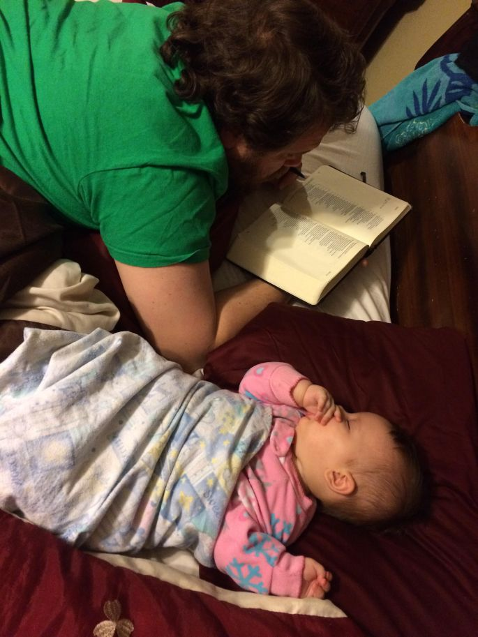 Dad reading Bible with Baby
