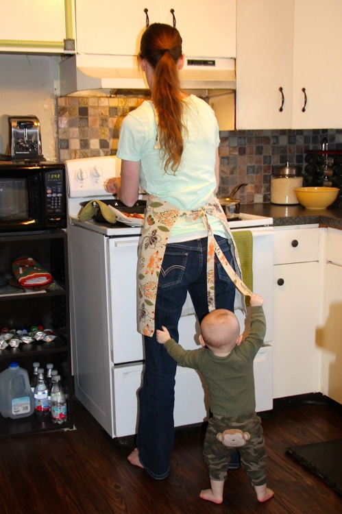 Baby playing with Mother's apron strings