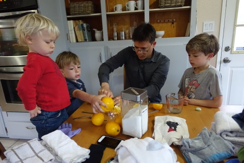 Father making lemonade with kids