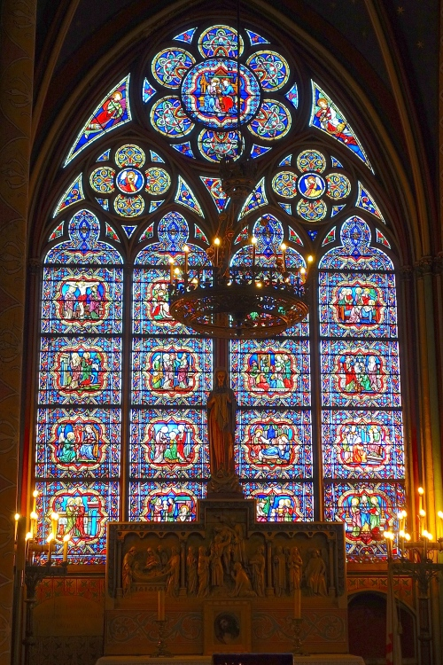 Cross in front of stained glass window Notre Dame Cathedral. Paris