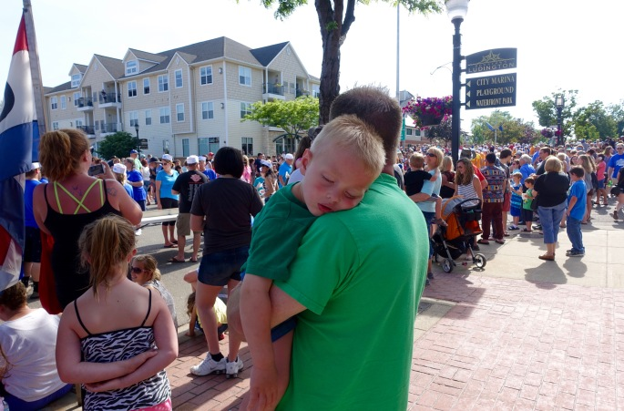 Little boy asleep in his father's arms at Ludington's World's Largest Sundae Attempt