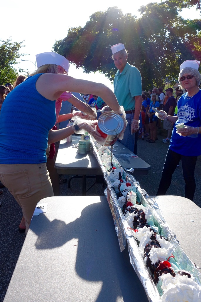 Pouring Chocolate syrup on top at Ludington's World's Largest Sundae Attempt
