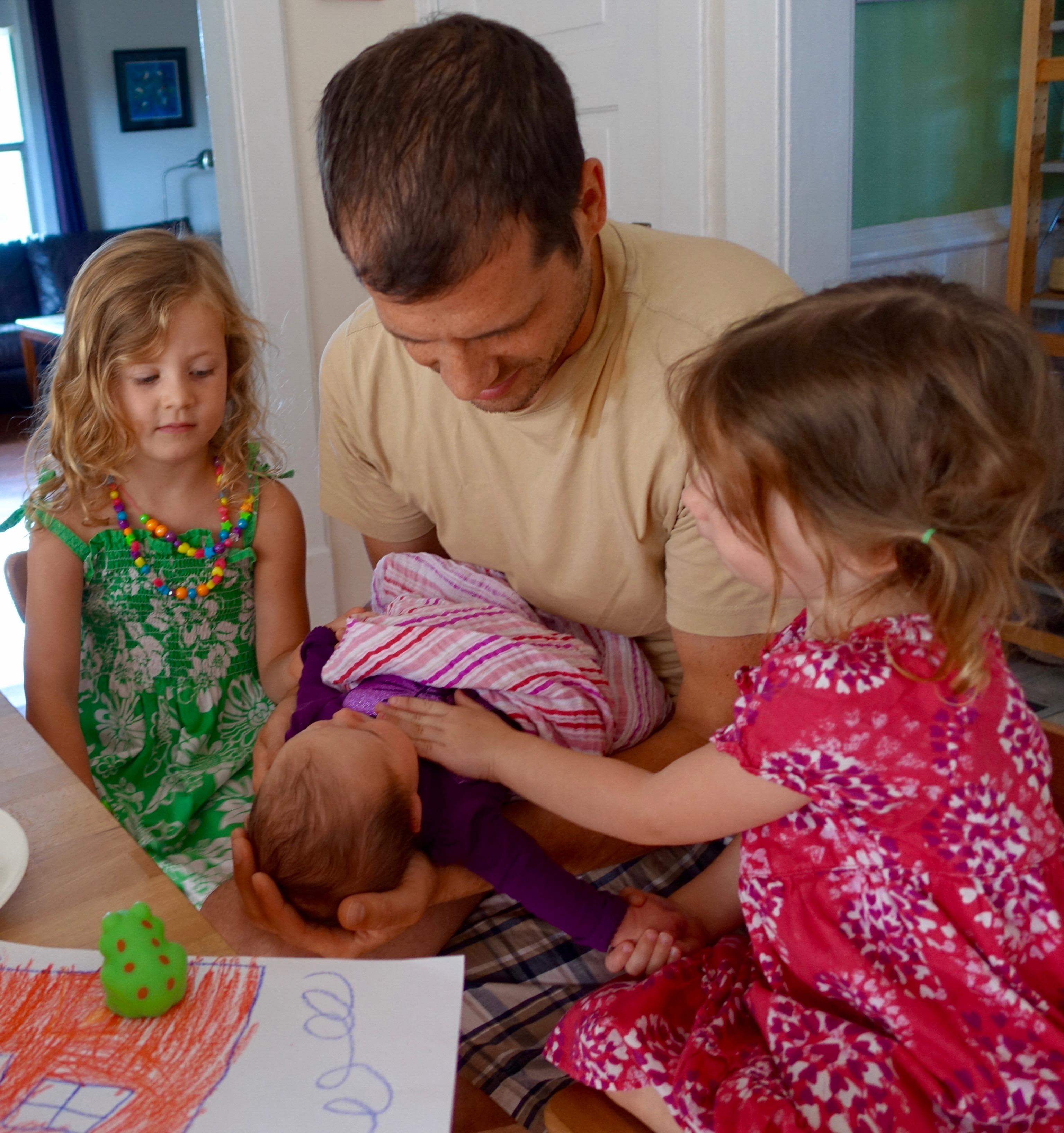 Children loving their new baby sister