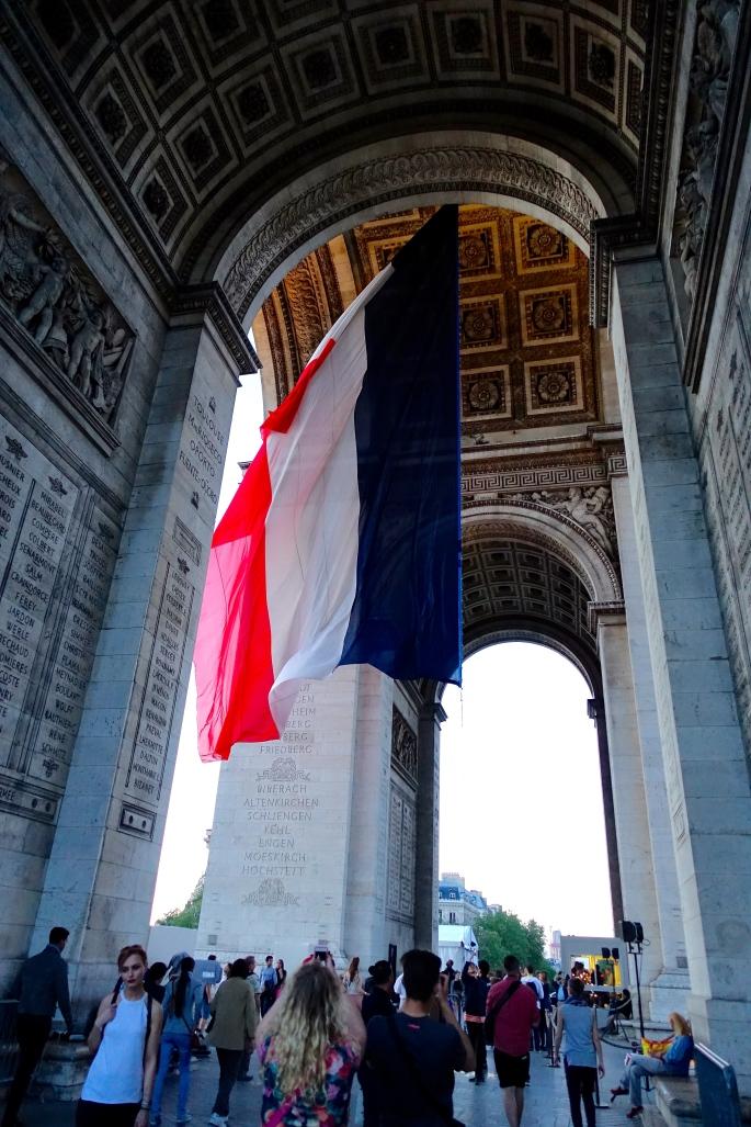 french-flag-under-arch-of-triumph