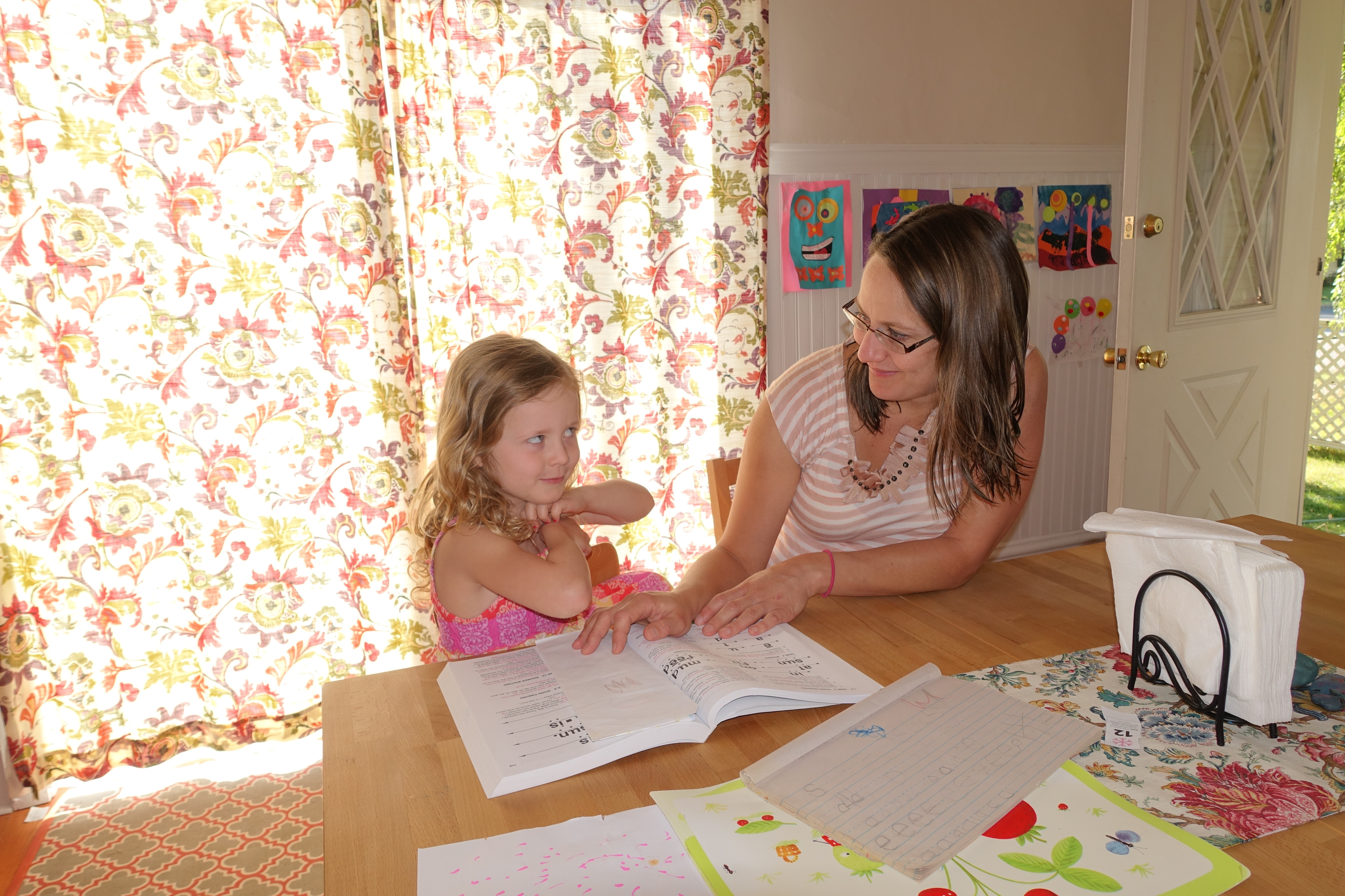 Mother helping daughter with reading