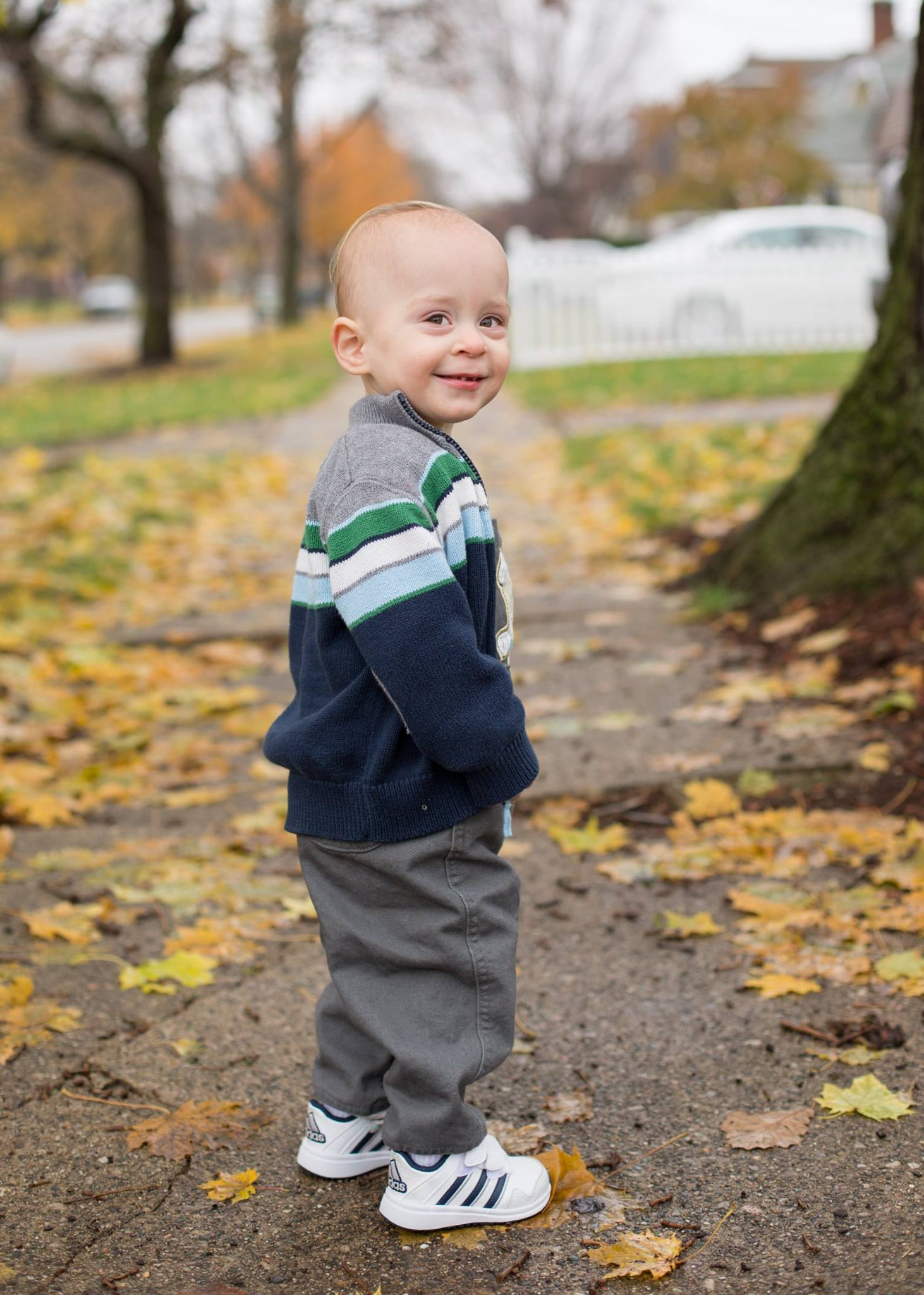 little-boy-walking-through-autumn-leaves