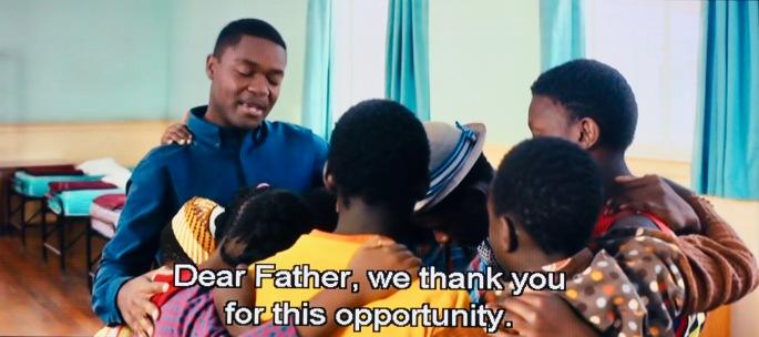robert-katende-praying-with-children-in-queen-of-katwe